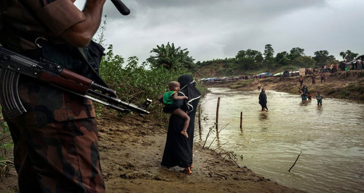 A Bangladeshi border guard sending Rohingya back across the border into their makeshift camp in Myanmar in August. CreditAdam Dean for The New York Times