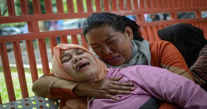 Relatives of man who died after consuming tainted homemade alcohol cry outside of a hospital in Cicalengka, Bandung Regency, West Java, Indonesia April 9, 2018. Photo: Reuters