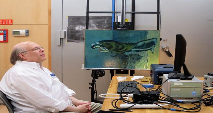 This handout picture shows Washington-based National Gallery of Art researcher John Delaney sitting next to the original painting of `Mother and Child by the Sea` by Picasso in 1902, during his research at Pola Museum of Art in Hakone, Kanagawa prefecture. Photo: AFP
