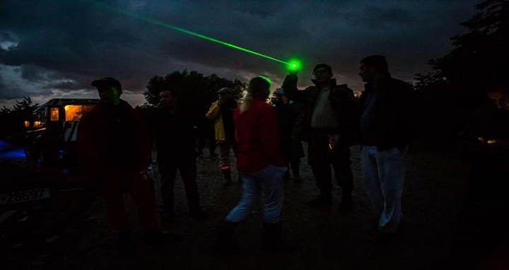 Inhabitants from Bacel village are using a laser pointer to light the way back for the Romanian General Emergency Inspectorate boats which are attempting to carry stranded people to safety on 30 June 2018, in Covasna county, Romania. Photo: AFP