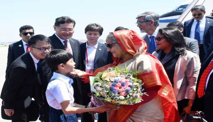 বুধবার প্রধানমন্ত্রী শেখ হাসিনা বেইজিং ক্যাপিটাল আন্তর্জাতিক বিমানবন্দরে পৌঁছলে তাঁকে একটি শিশু ফুল উপহার দেয় -পিআইডি