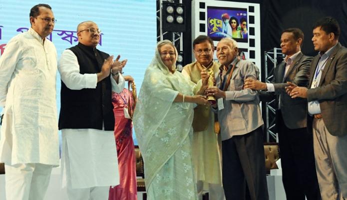 রবিবার প্রধানমন্ত্রী শেখ হাসিনা ঢাকায় বঙ্গবন্ধু আন্তর্জাতিক সম্মেলন কেন্দ্রে জাতীয় চলচ্চিত্র পুরস্কার ২০১৭ ও ২০১৮ প্রদান অনুষ্ঠানে চলচ্চিত্র অবিনেতা এ টি এম শামসুজ্জামানকে সম্মাননা পুরস্কার প্রদান করেন -পিআইডি